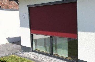 Red zipscreen in front of a floor-to-ceiling window